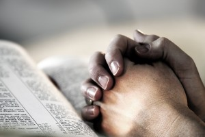 bigstock-Praying-hands-bible-283463